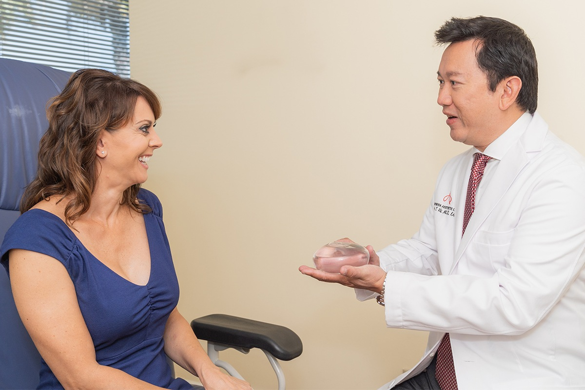 Dr. Vu Showing A Female Patient An Implant During a Consultation