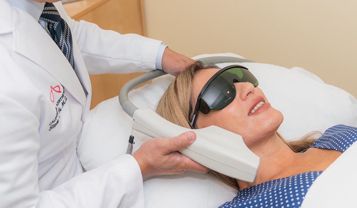Dr. Vu Using Photofacial Device on Female Patient's Face While She Wears Protective Eyewear
