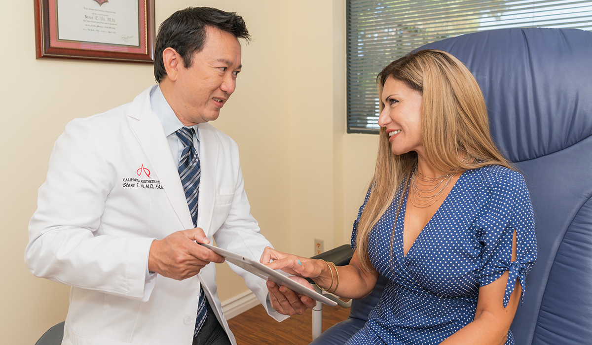 A Female Patient Touching a Tablet Held by Dr. Vu During a Consultation