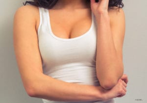 Closeup of Woman's breasts with a white tank top