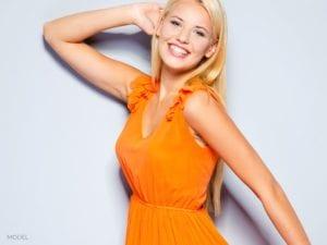 Portrait of female in orange dress posing
