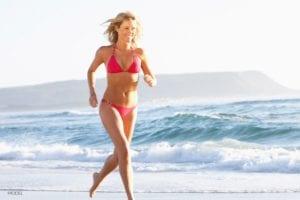 Female in red bikini running on beach